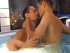 Two young handsome dudes frisking in swimming pool